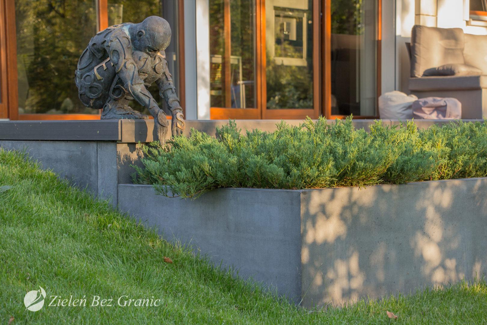 Taras zwieńczony donicą z betonu architektonicznego.