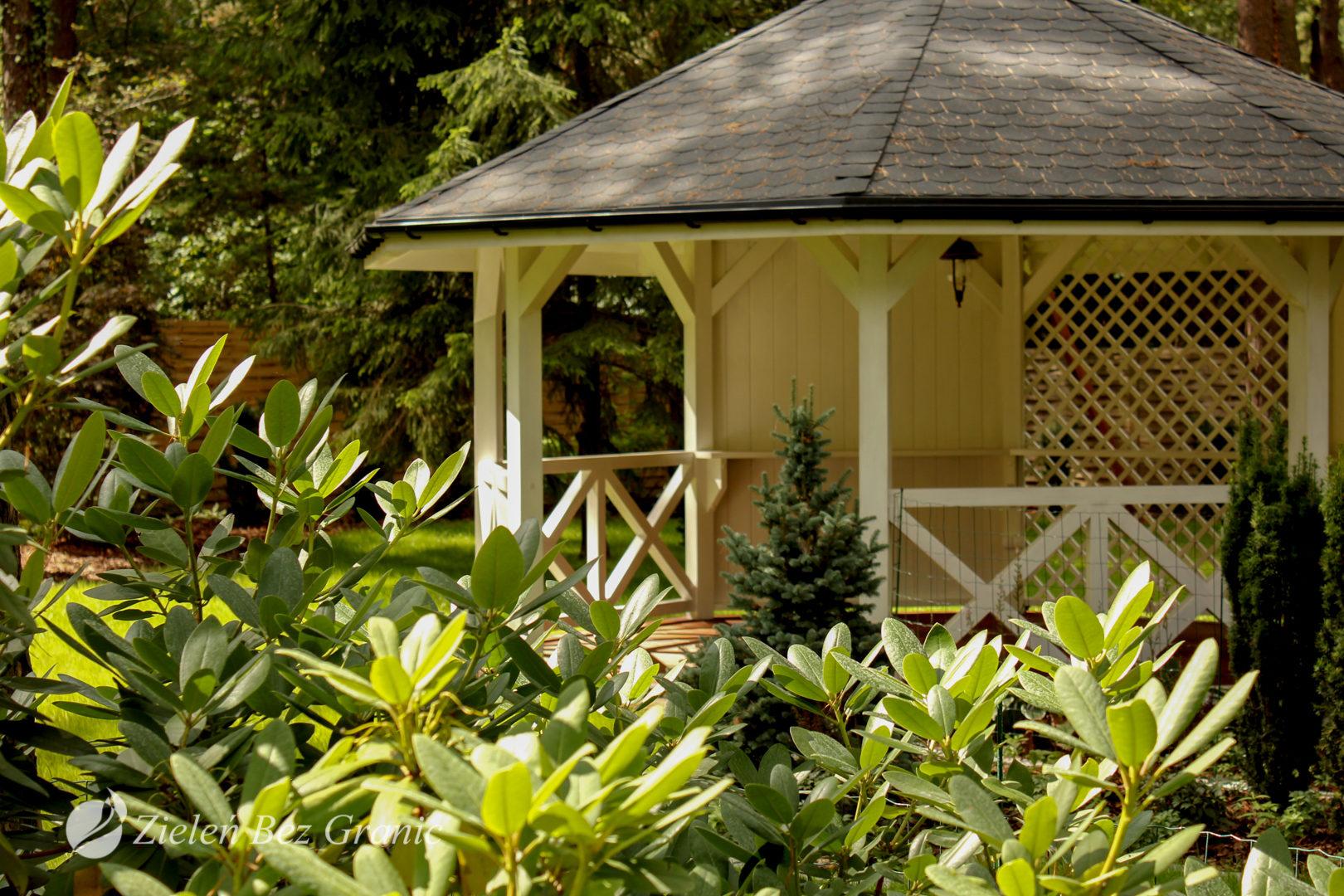 Drewniana altana w ogrodzie leśnym.